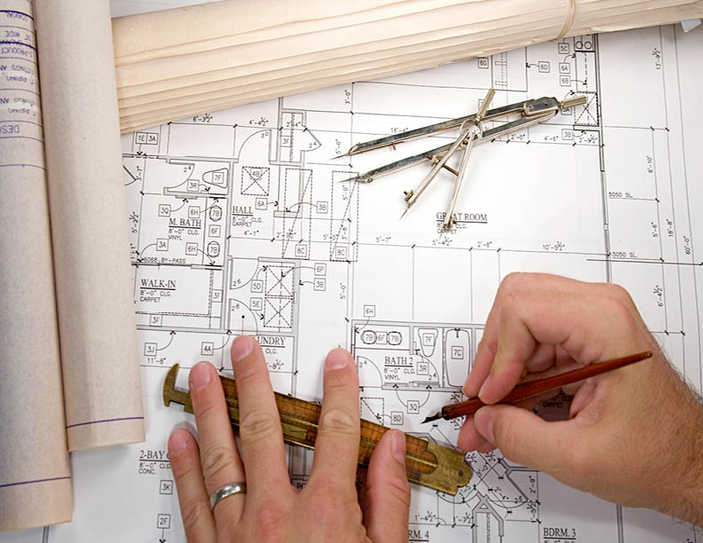 Man drawing on a bathroom design blueprint for bathroom countertop installation.